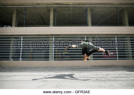 Young man doing parkour against fence in urban alley - Stock Photo