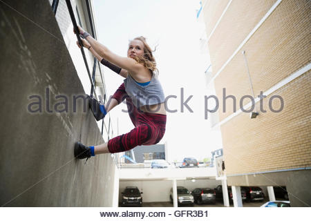 Young woman doing parkour along urban wall - Stock Photo