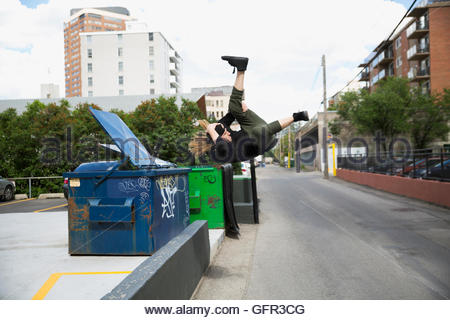 Cool young man doing parkour at dumpster in urban street - Stock Photo