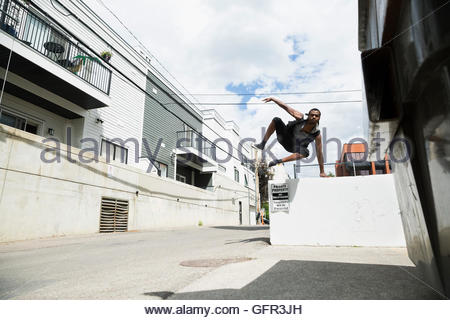 Young man doing parkour free running in sunny urban alley - Stock Photo