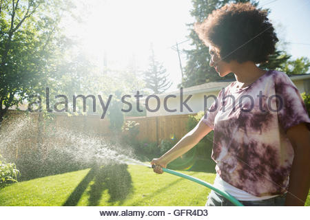 Woman watering garden in sunny backyard - Stock Photo