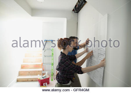 Couple holding blueprint against wall for home improvement project - Stock Photo