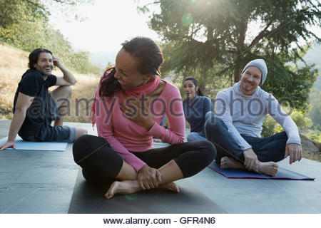 Laughing friends after yoga class on deck - Stock Photo