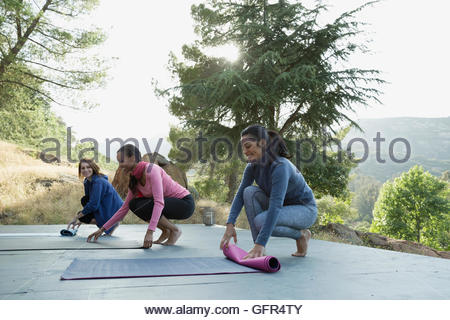 Women rolling up yoga mats after class on deck - Stock Photo