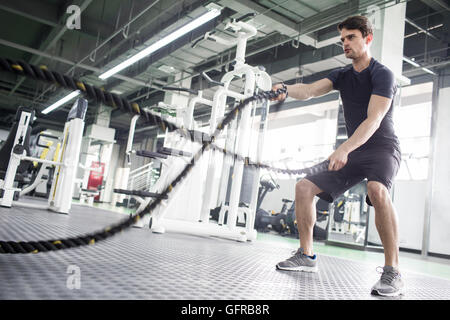 Young man exercising with battling rope at gym - Stock Photo