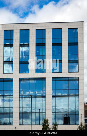 Modern office block with blue sky reflected in dark windows - Stock Photo