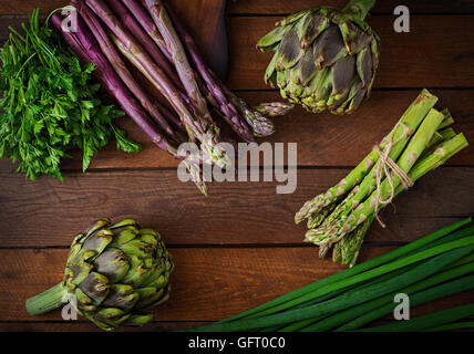 Asparagus and artichokes with herbs on a wooden background. Top view - Stock Photo