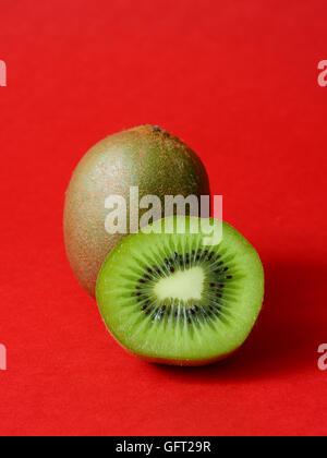 Juicy kiwi fruit on a red background - Stock Photo