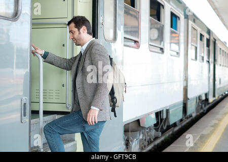 standing man leaving on the train in a train station platform - Stock Photo