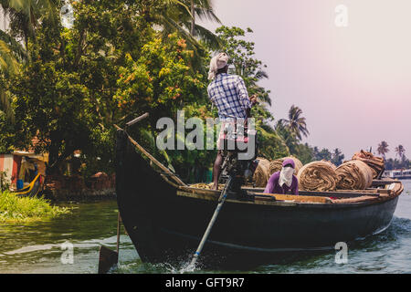 Allepey, Kerala, India March 31, 2015: Indian man transport dwell with rice for boats. backwaters canoe in state,. - Stock Photo