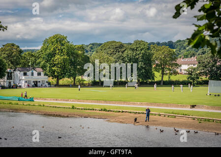 A cricket match being played at Saltaire Cricket Club in Roberts Park by the river Aire in Saltaire West Yorkshire. - Stock Photo