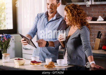 Couple looking at tablet while having breakfast - Stock Photo