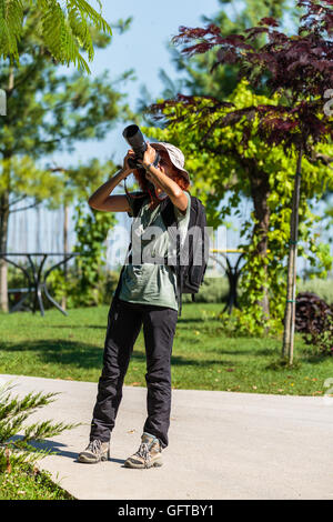 Professional nature photographer lady with her camera in the field - Stock Photo