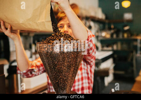 A woman pouring coffee beans into a grinder hopper in a coffee shop - Stock Photo
