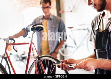 Two men in a cycle repair shop looking at a bicycle One holding a smart phone and card processing contactless payment - Stock Photo