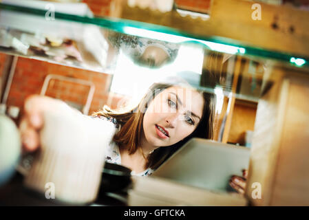 Young woman in a shop holding a digital tablet and a ceramic mug - Stock Photo