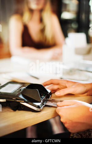 Close up of a woman using a credit card reader in a shop - Stock Photo