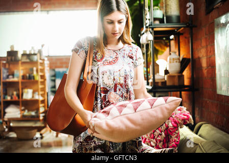 Young woman standing in a shop holding a cushion - Stock Photo