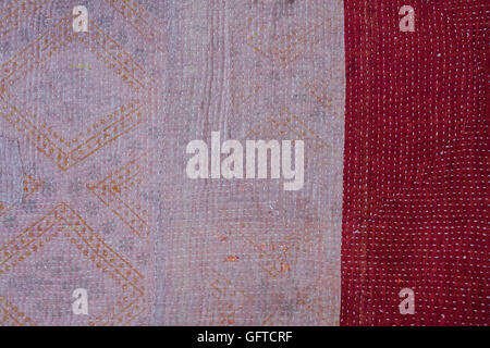 Full frame view of an antique bedspread patterned fabric with a faded strip and a red border with small running - Stock Photo