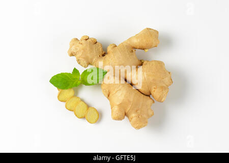 fresh ginger root on off-white background with shadows - Stock Photo