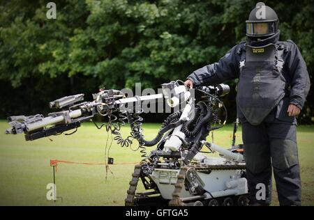Kineton EOD (Explosive Ordnance Disposal) operator dressed in a bomb suit with a bomb-disposal robot. - Stock Photo