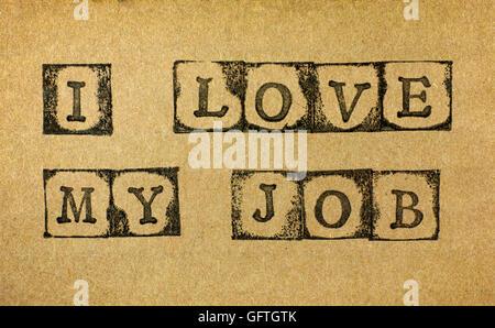 Words I Love My Job make by black alphabet stamps on cardboard. - Stock Photo