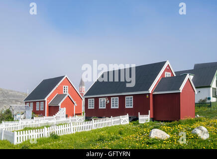 Traditional red Greenlandic houses with fenced gardens in summer. Colonial Harbour (Kolonihavnen), Nuuk, Greenland - Stock Photo