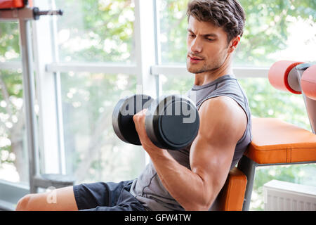Concentrated young sportsman doing exercises for biceps using dumbbells in jym - Stock Photo
