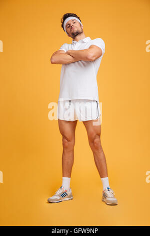 Serious confident young sportsman standing with arms crossed over yellow background - Stock Photo