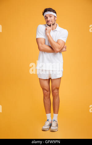 Pensive amusing young sportsman standing with hands folded and thinking over yellow background - Stock Photo