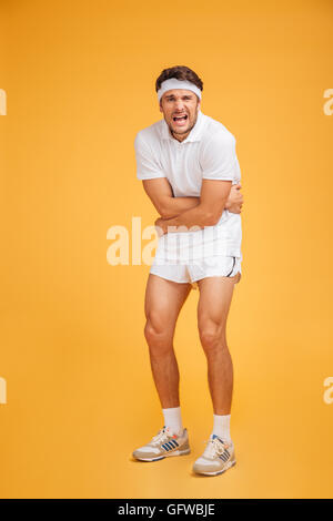 Unhappy young man athlete standing and having a stomach ache over yellow background - Stock Photo