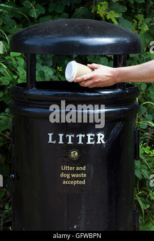 Man putting a non-recyclable coffee cub in a litter bin - Stock Photo