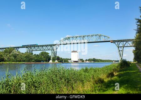 Commuters train crossing Hochdonn High Bridge, a historic railway bridge across Kiel Canal at Hochdonn - Stock Photo