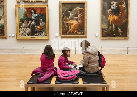 Children art gallery, a mother and her two daughters view 17th century art paintings in the Louvre Museum in Paris, - Stock Photo