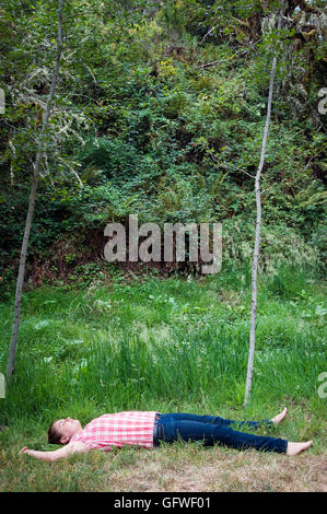 A young girl laying down in the grass. - Stock Photo