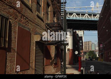 View down Plymouth Street in DUMBO Brooklyn looking toward the Manhattan and Brooklyn bridges - Stock Photo