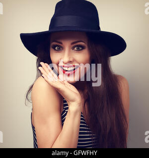 Happy bright makeup surprising woman looking funny in fashion blue hat. Toned vintage portrait - Stock Photo
