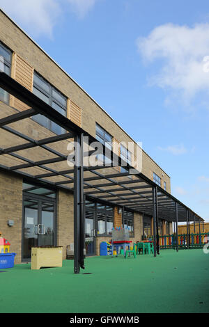 A glazed roof covers an outside play area at a new London primary school. Show soft surface for safety. - Stock Photo