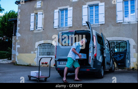 Loading up a a Ford Transit van with wine bought on holiday in France - Stock Photo