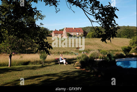 Woman on holiday enjoys late afternoon sun at gite  in Le Lot Region department South West France Midi Pyrenees - Stock Photo