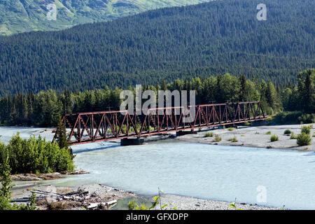 Classic Railroad trestle crossing glacier-fed Snow river. - Stock Photo