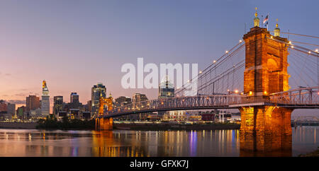 Image of Cincinnati and John A. Roebling suspension bridge at twilight. - Stock Photo