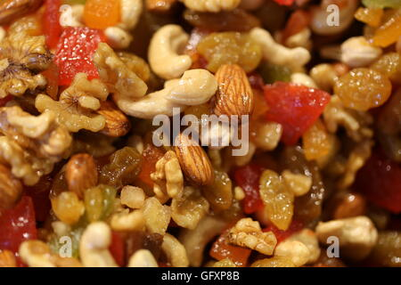 Candied Fruits and Dehydrated Fruits, close up. Stack of crystallized fruits: Cashews, walnuts, almonds, raisins, - Stock Photo