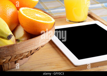 Fresh fruits and a Tablet PC on wooden table. Healthy eating concept