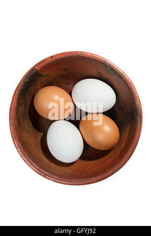 four eggs, two red and two white, in a bowl isolated on white background - Stock Photo