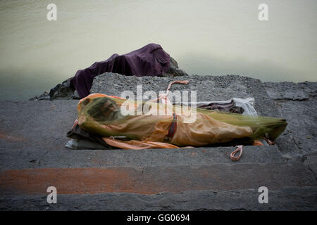 Rishikesh, Uttarakhand, India. 17th May, 2013. File Image - A Sadhu covered by a mosquito net rests at banks of - Stock Photo