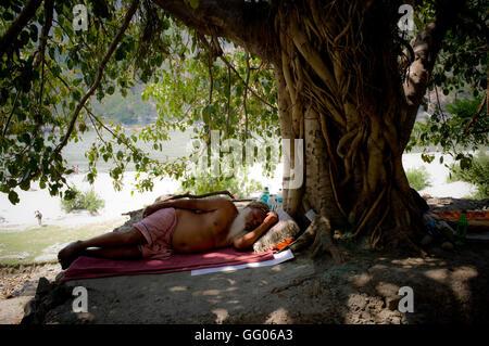 Rishikesh, Uttarakhand, India. 17th May, 2013. File Image - A Sadhu man rests at banks of the Ganges river in Rishikesh, - Stock Photo