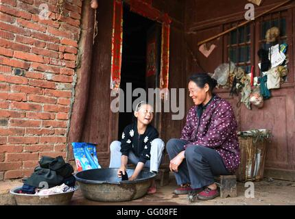 (160803) -- XUNDIAN, Aug. 3, 2016 (Xinhua) -- 10-year-old He Yuanxi helps her grandmother wash clothes in Fengle - Stock Photo