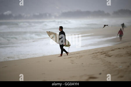Rio de Janeiro, Brazil. 3rd Aug, 2016. A surfer walks with his board in the water at a beach in Barra prior to the - Stock Photo