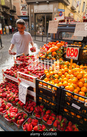 Italian street market seller with his top quality fresh fruit –strawberries & oranges – and vegetables, stall, - Stock Photo